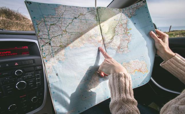 persona-vistiendo-suéter-beige-sosteniendo-mapa-dentro-vehículo-1252500